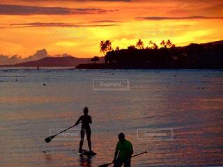 水の体の上の夕日の前に立っている男の写真・画像素材[2086308]
