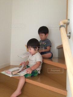 階段で兄弟仲良く絵本の写真・画像素材[2184803]