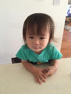 テーブルの上に座っている小さな男の子の写真・画像素材[2284683]