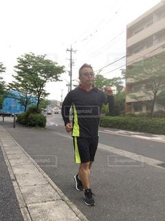 通りをウォーキングする男の写真・画像素材[2108813]
