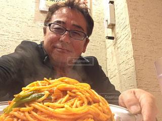 食べ物を食べるテーブルに座っている男の写真・画像素材[2269044]