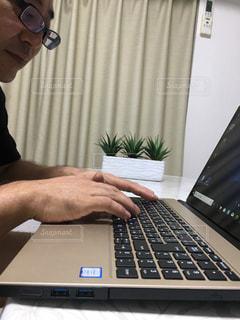テーブルの上に座っているラップトップコンピュータを使っている男の写真・画像素材[2311744]