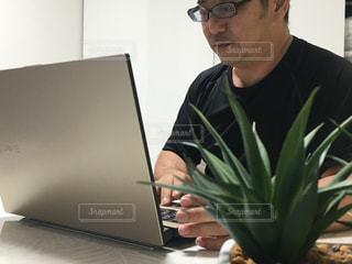 ラップトップコンピュータを使ってテーブルに座っている男の写真・画像素材[2311769]