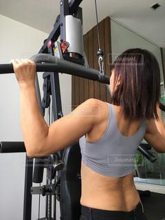 トレーニングマシーンを操る女性の写真・画像素材[2386374]