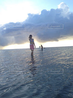 水域の近くの浜辺に立っている女性の写真・画像素材[2422251]