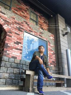 レンガ造りの建物の前のベンチに座っている男の写真・画像素材[2424638]
