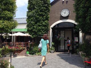 歩道に時計を置く建物の前に立っている女性の写真・画像素材[2425029]