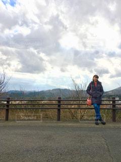 フェンスの前に立っている女性の写真・画像素材[2427548]