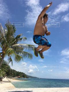 ビーチで空中に飛び込む若者の写真・画像素材[2980495]