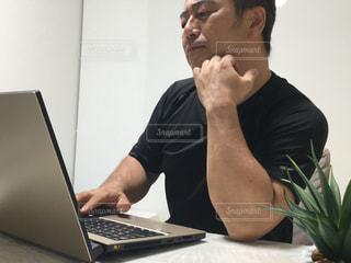 テーブルの上に座っているラップトップコンピュータを使っている男の写真・画像素材[3231047]