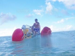 水の中でボートの後ろに乗っている男の写真・画像素材[3556439]