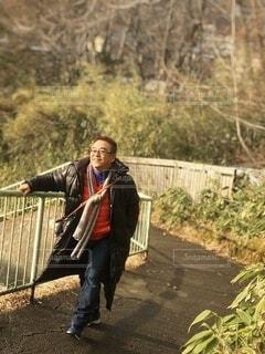 フェンスの隣に立っている人の写真・画像素材[3856682]