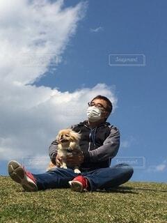 芝生で覆われた畑の上に座っている男の写真・画像素材[3965308]