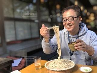 食べ物を持ってテーブルに座っている男の写真・画像素材[4000027]