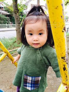 遊び場の前に立っている小さな女の子の写真・画像素材[2096629]