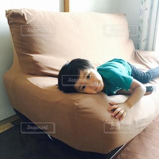 ソファーに横たわっている少年の写真・画像素材[2099023]