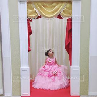 赤いカーテンの女の子の写真・画像素材[2121296]