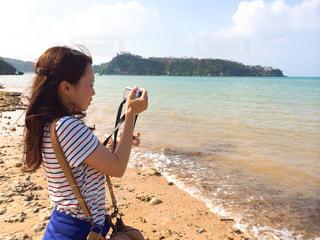 女性,20代,海,夏,カメラ,カメラ女子,太陽,ボーダー,日焼け,海岸,沖縄,洋服,Tシャツ,昼,シャツ,夏服,半袖