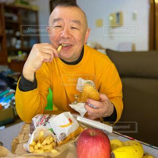 男性,食べ物,飲み物,食事,食卓,リビング,屋内,ハンバーガー,果物,野菜,机,人物,人,座る,笑顔,食べる,大人,料理,休日,出前,フライドポテト,宅配,テイクアウト,ファストフード,お父さん,スナック,中年,リンゴ,デリバリー,お持ち帰り,コロナ禍