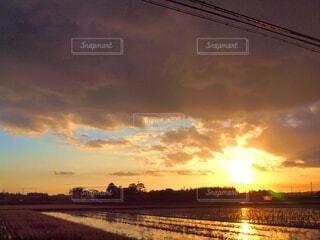 夕陽と雲と水田との写真・画像素材[4825674]