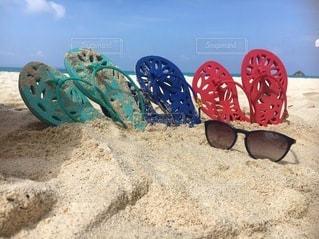砂の中に横ビーチとサンダルとサングラスの写真・画像素材[3478866]