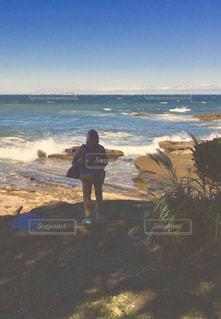 岩場の海岸に立つ男の子の写真・画像素材[2514016]