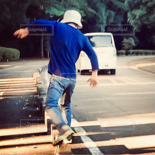 散歩中、道路の路肩を跳びながら移動する子供。の写真・画像素材[2514126]