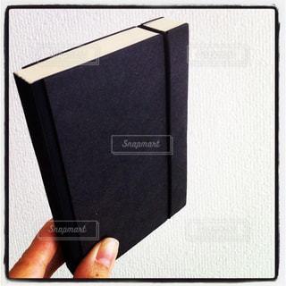 黒いスケジュール帳と手元の写真・画像素材[3020029]