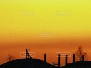 オレンジ色の夕焼けと人影の写真・画像素材[3475401]
