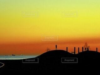 オレンジ色の夕焼けと人影の写真・画像素材[3475400]