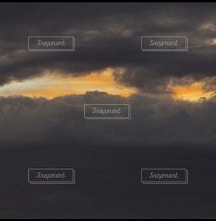 暗い雲の隙間に見えたオレンジの雲の写真・画像素材[3485810]