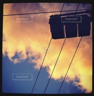 夕焼け雲背景の信号機のシルエットの写真・画像素材[4418332]
