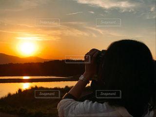 女性,自然,風景,空,カメラ,夕日,屋外,太陽,雲,後ろ姿,夕焼け,夕暮れ,水面,山,景色,水田,撮影,光,人物,人,後姿,旅行,写真,サンセット,オレンジ色,腕まくり