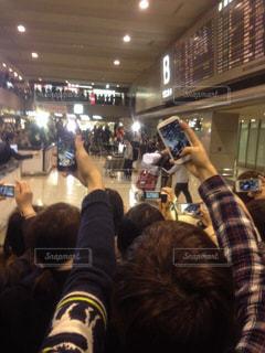 カメラ,群衆,屋内,後ろ姿,ライト,人,後姿,空港,トランク,立つ,カート,たくさん,携帯,右手,電光掲示板,到着,帰国,到着ロビー