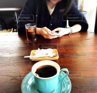 コーヒーを飲みながらテーブルに座っている人の写真・画像素材[2285136]