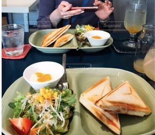 食べ物の皿を持ってテーブルに座っている女性の写真・画像素材[2288819]