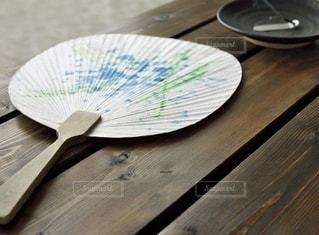 木製のテーブルの上に置いたうちわの写真・画像素材[3594963]