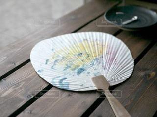 木製のテーブルの上に置いたうちわの写真・画像素材[3594965]