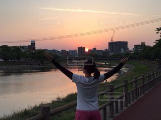 夕日,後ろ姿,川,人物,人,後姿,ジョギング,ランニング,飛行機雲,夕陽,川沿い