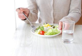 食べ物の皿を持ってテーブルに座っている女性の写真・画像素材[2831316]
