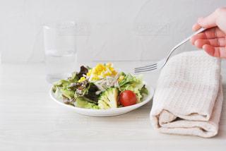 食べ物の皿をテーブルの上に置く人の写真・画像素材[2831317]