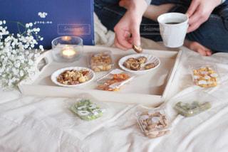 食べ物の皿を持ったテーブルに座っている人の写真・画像素材[3023406]