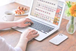 ラップトップコンピュータを使ってテーブルに座っている人の写真・画像素材[3191679]