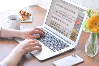 テーブルの上に座っているラップトップコンピュータを使っている人の写真・画像素材[3191687]