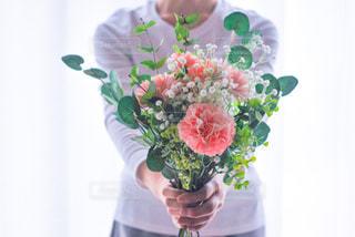 花で満たされたガラスの花瓶を持つ手の写真・画像素材[3192401]