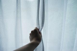 カーテンを持つ手の写真・画像素材[3322588]