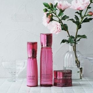テーブルの上にピンクの花で満たされた花瓶の写真・画像素材[3387794]