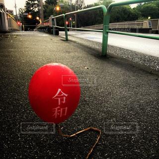 道路の脇に座っている赤い風船の写真・画像素材[2103000]