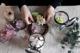 食べ物を持ってテーブルに座っている人の写真・画像素材[2875284]