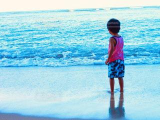 水域の隣に立っている若い少年の写真・画像素材[2130394]